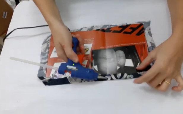 Dùng súng gắn keo gắn vải lót với mảnh giấy mỏng vừa chuẩn bị