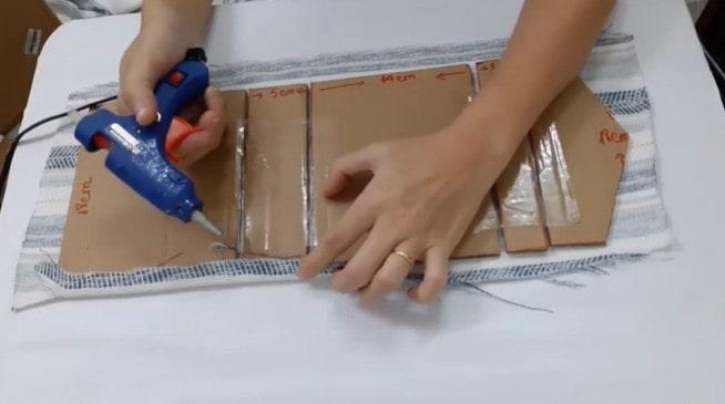 Dùng súng gắn keo dính vải và giấy lại với nhau